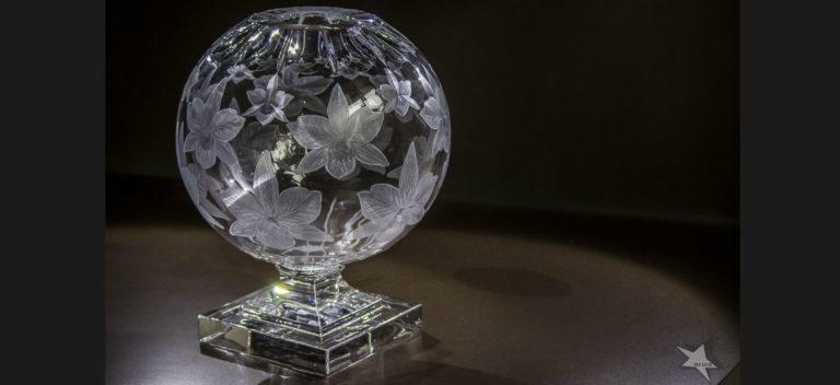 Vaso sfera in cristallo soffiato (h 28cm), inciso con fiori di orchidee in tre misure a scalare e molature per enfatizzare la luce. A cura di Vanessa Cavallaro © Ida Luce