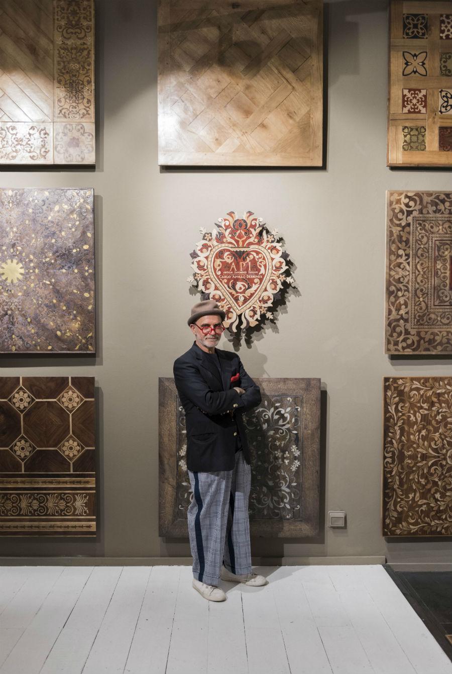 Il Maestro Carlo Apollo fra i suoi meravigliosi pannelli lignei, in un'installazione temporanea.