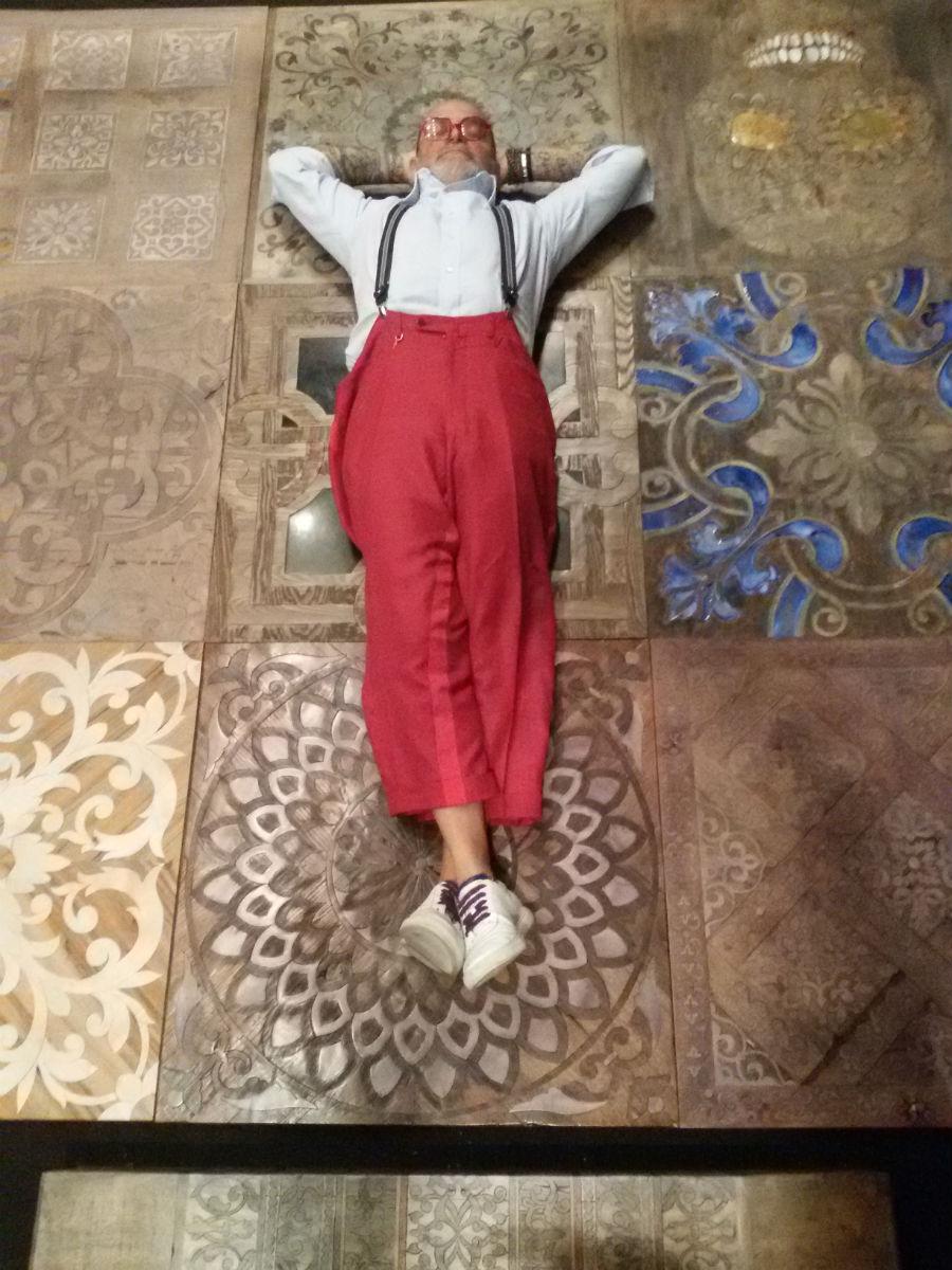 Carlo Apollo in un momento di relax divertito sui suoi pavimenti in legno nello show room di Milano: lo spirito ludico e l'ironia sono parte della personalità di questo maestro.