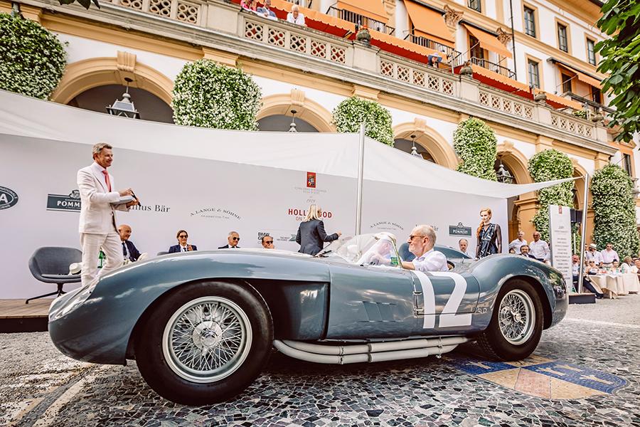 """La splendida Ferrari 335 Sport carrozzata Scaglietti del 1958 vincitrice del premio Best of Show 2018 del Concorso d'Eleganza Villa d'Este sfila sotto lo sguardo di Simon Kidston, esperto di auto classiche nonché """"voce"""" ufficiale dell'evento."""