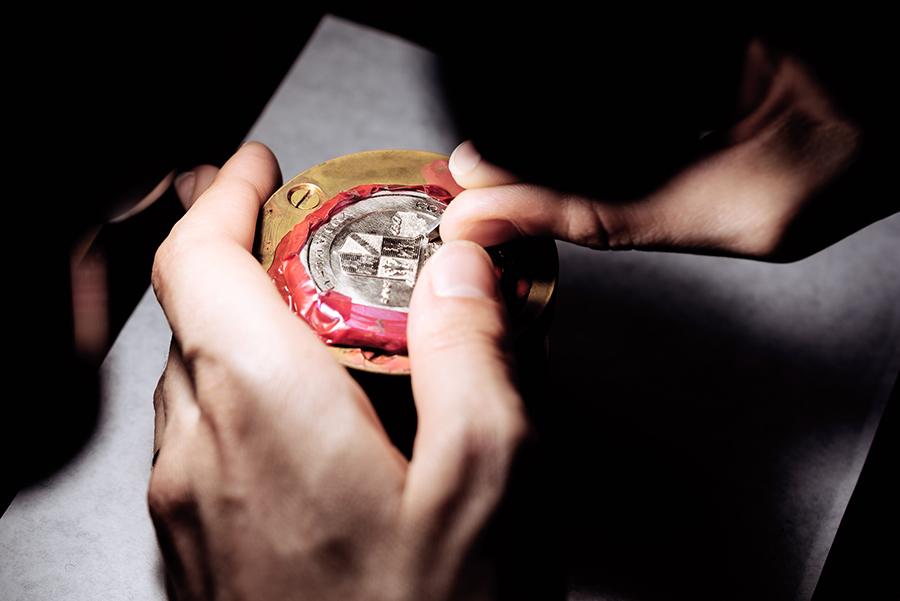 """Un momento dell'incisione, rigorosamente manuale, del fondello del Lange 1 Time Zone """"Como Edition"""" con lo stemma della competizione del Concorso d'Eleganza Villa d'Este. Lavorazione che rende di fatto l'orologio, un pezzo unico."""