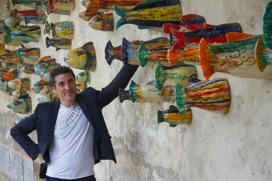 """Nicolò Morales al centro della sua scultura parietale con i pesci in occasione di """"Mediterranea"""". Il gruppo scultoreo è stato presentato per Expoarteitaliana, a cura di Vittorio Sgarbi, a Villa Bagatti Valsecchi a Varedo (MB). La tematica è tutta centrata sul mare e il suo ecosistema, sull'acqua come fonte di vita e di ispirazione. Photo credit: Morales Ceramiche di Caltagirone"""