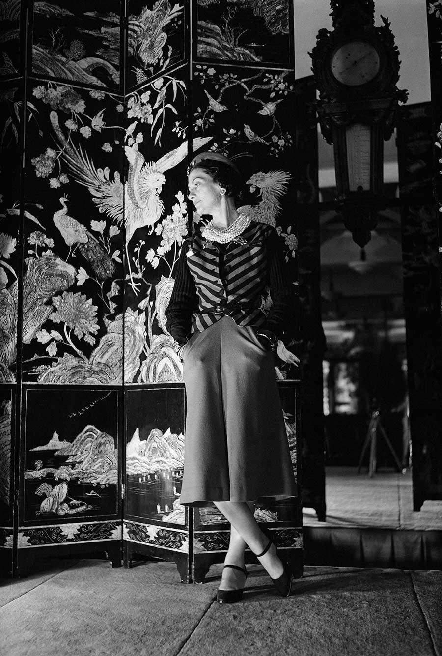 Mademoiselle Coco ritratta accanto ad uno dei paraventi Coromandel, ispirazione della nuova collezione di gioielli Chanel