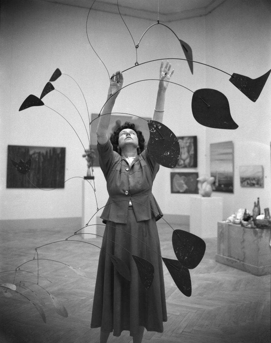 Peggy Guggenheim al padiglione greco con Arco di petali (1941) di Alexander Calder, XXIV Biennale di Venezia, 1948 / Peggy Guggenheim next to Alexander Calder, Arc of Petals (1941), Greek Pavilion, 24th Venice Biennale, 1948