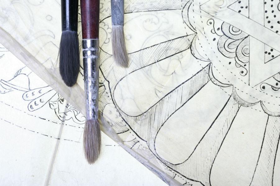 Maiolica di Gubbio - Ceramiche Biagioli:Particolare dei cartoni preparatori detti spolveri. Il cartone preparatorio, precedentemente forato e che riproduce i contorni di un disegno, viene appoggiato sulla superficie da decorare: con un pomaccio di carbone o sanguigna si tamponano le parti perforate. Questa tecnica serve per tracciare le linee guida di un determinato decoro e suddividere gli spazi. Dopo la cottura le tracce di carbone svaniscono. Courtesy Ceramiche Biagioli