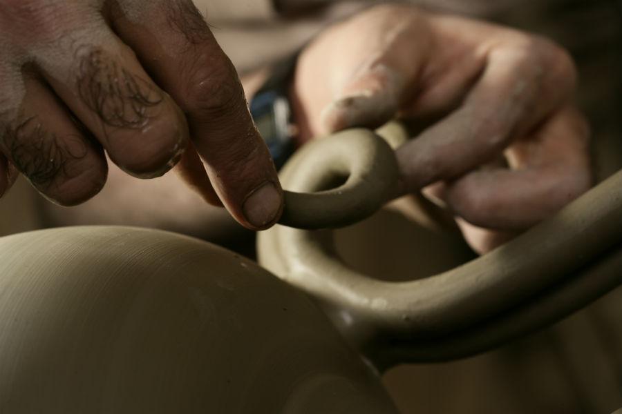 Maiolica di Gubbio - Ceramiche Biagioli: Particolare dell'applicazione dei manici di argilla sul corpo di un vaso a metà fase di essiccazione. L'asciugatura deve avvenire lentamente, specie nella prima fase, in quanto la quantità di acqua contenuta nel pezzo è ancora eccessiva. Courtesy Ceramiche Biagioli