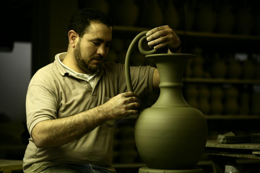 Maiolica di Gubbio - Ceramiche Biagioli: Particolare dell'applicazione dei manici in argilla. L'argilla ha la proprietà di assorbire fino al 70% di acqua e, bagnata, si lascia modellare in modo da assumere la forma desiderata. Courtesy Ceramiche Biagioli