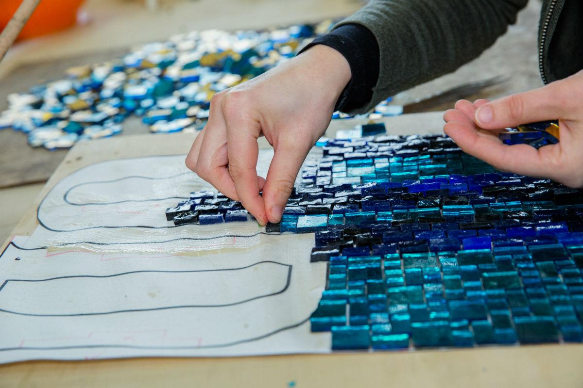 Particolare di lavorazione del mosaico. Le tessere, dopo essere state sminuzzate e tagliate della misura desiderata, vengono applicate su una base cartacea dove è stato preventivamente tracciato il disegno a grandezza reale. In questa fase vengono definiti tutti i dettagli, dall'andamento delle tessere al chiaroscuro. ©Susanna Pozzoli