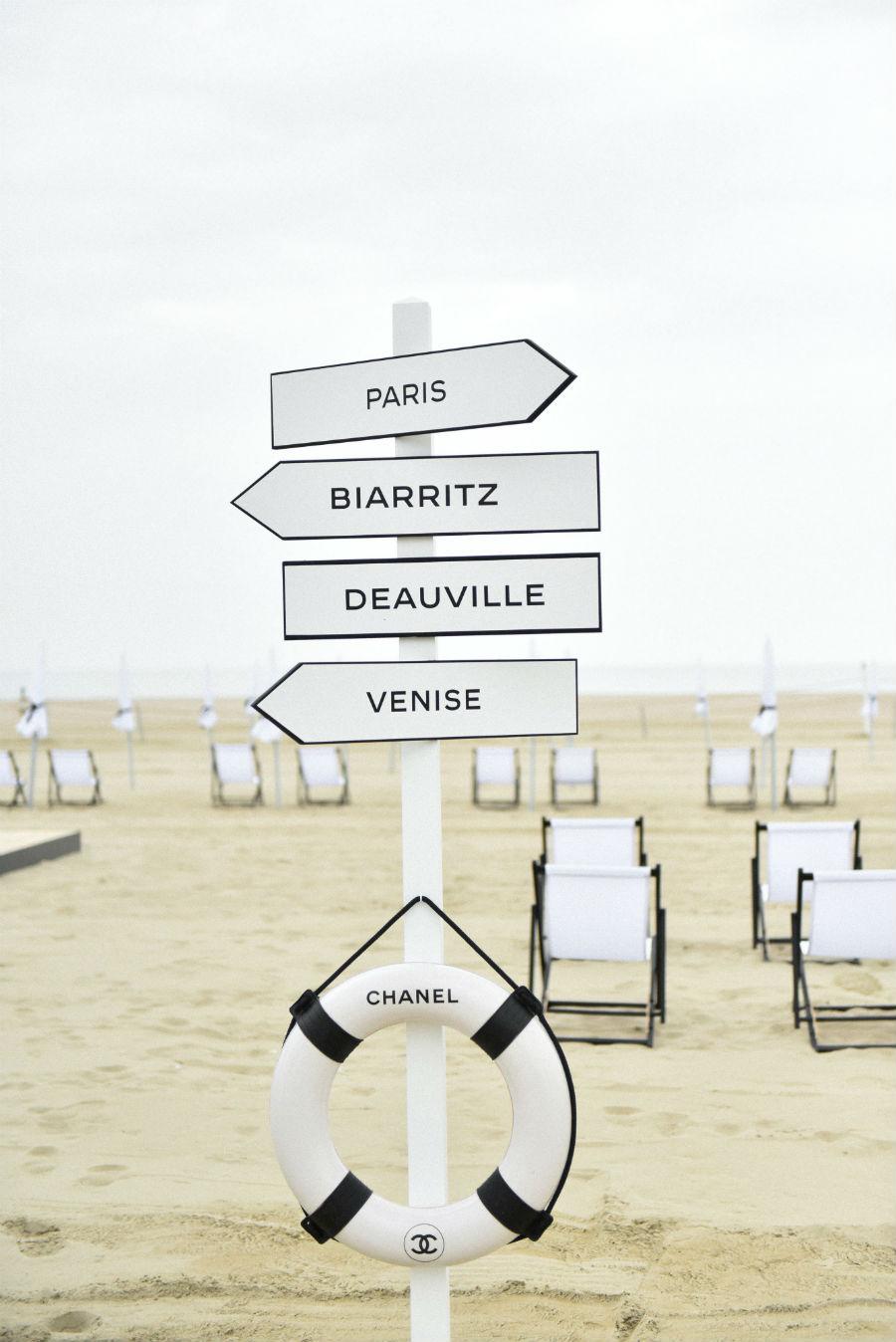 Profumi Chanel - collezione Eaux de Chanel: un cartello sulla spiaggia che indica le 4 destinazioni Paris, Biarritz, Deauville e Venise