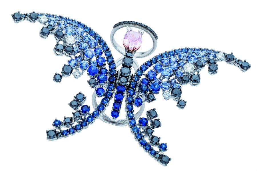 Collezione Animalia, Damiani Gioielli: anello in oro bianco, accoglie un oval fancy purplish pink di 2,23 carati, circondato dall'intensità degli zaffiri che disegnano la leggerezza delle ali nelle diverse tonalità del blu.