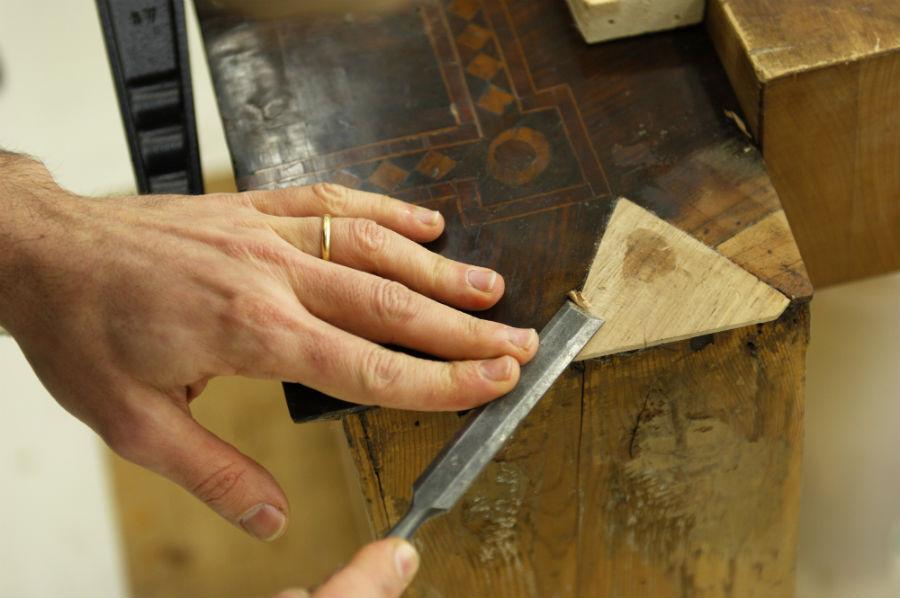 Un Maestro al lavoro su un pezzo di arredo per il suo restauro