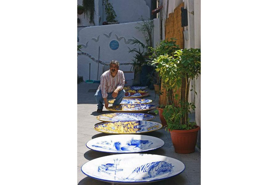 Vietri sul mare: Il Maestro è ritratto accanto ai grandi piatti (100cm di diametro), che esprimono il suo stile ricco di citazioni colte, tradizionale e innovativo insieme. Le sue opere sono molto apprezzate da estimatori di ceramica, architetti, designer di tutto il mondo.