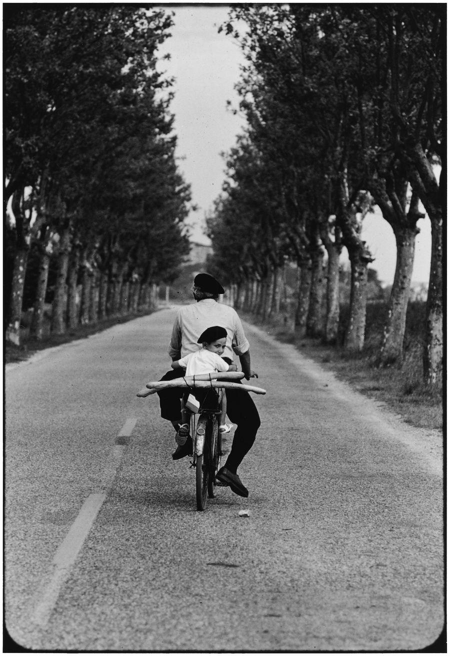 Elliott Erwitt in mostra a Pavia con Icons: nell'immagine FRANCE. Provence. 1955 © Elliott Erwitt/MAGNUM PHOTO, padre e figlio in bicicletta