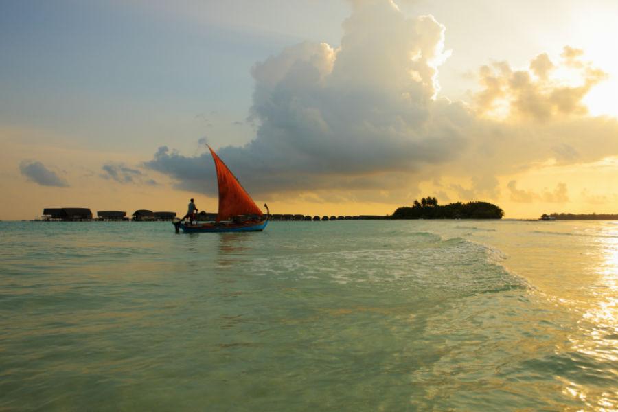 Cocoa Island, resort di lusso a Makunufushi - Maldive: nell'immagine una veduta notturna del resort dal mare al tramonto