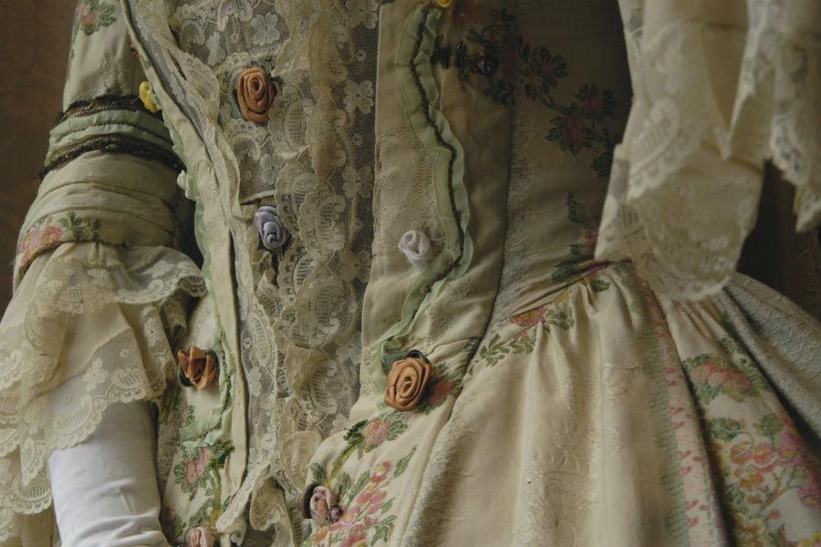Nicolao Atelier: Dettaglio delle decorazioni di un costume d'epoca del XVIII secolo: realizzato in liseré fiorato, davantino in pizzo e fiori applicato. Tutte le fasi di lavorazione vengono realizzate a mano.