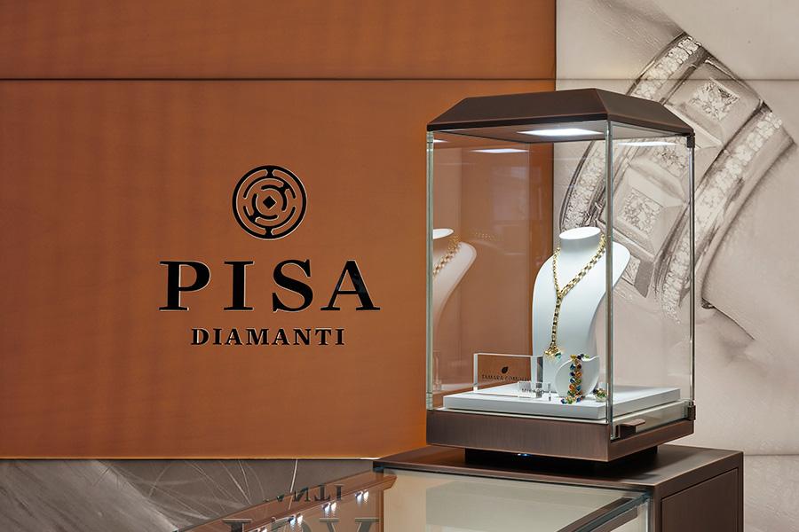 Un'immagine de il Salone Gioielli di Pisa Orologeria: progettato a cura di Vittorio Carena Studio, si estende in uno spazio di oltre 100 mq con banchi circolari, teche in metallo e tessuti preziosi, sovrastati da un'installazione luminosa in vetro. Ospita anche uno spazio satellite dedicato al Salotto de Grisogono.