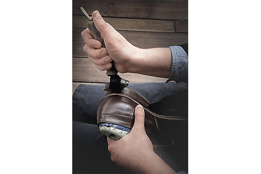 Scarpa su misura di Saskia Wittmer - ©Laila Pozzo: Un passaggio ulteriore è la rifinitura del tacco: dopo aver applicato sapone e acqua, Saskia passa con cura il bussetto di ghisa, precedentemente scaldato, per chiudere i pori e favorirne l'impermeabilizzazione.