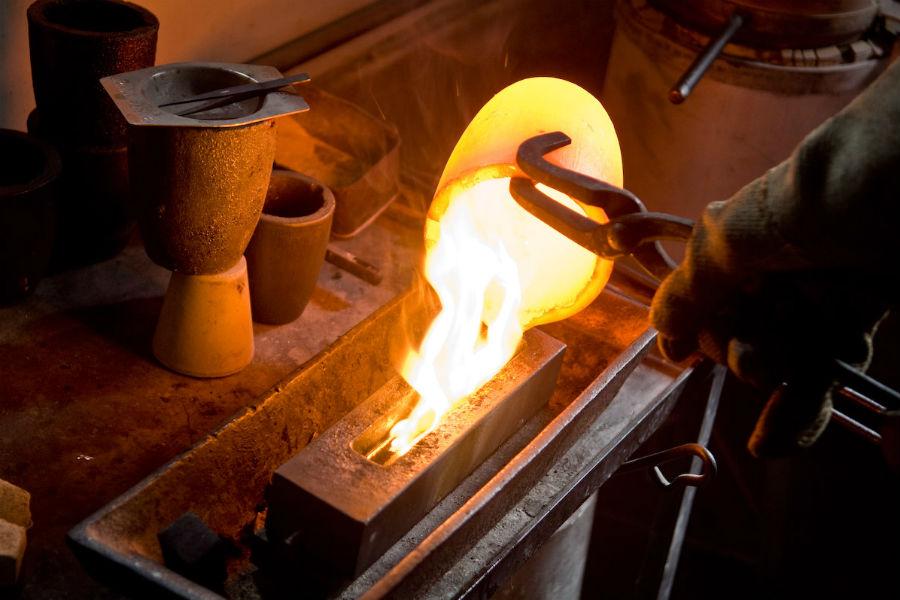 Particolare del procedimento di fusione dell'oro da parte del battiloro. Dopo aver raggiunto lo stato liquido, l'oro incandescente viene tolto dal crogiuolo e posizionato nella staffa, per creare un nuovo lingottino d'oro. Successivamente viene laminato fino a ottenere una lunga striscia sottile, dalla quale vengono tagliati dei piccoli quadrati, sottoposti prima alla battitura con il maglio e poi manuale da Marino Menegazzo. CreditsMarc de Tollenaere