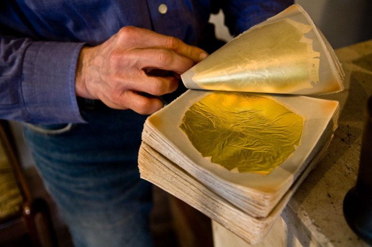 """Particolare del """"blocchetto"""" di fogli pergamino utilizzati per separare i quadrati d'oro. Qui si vede la foglia d'oro ottenuta dopo la battitura da parte del battiloro. Lo spessore varia in base al tempo impiegato a battere: si va dai 50 minuti per spessori maggiori, fino alle 2 ore per spessori sottilissimi."""