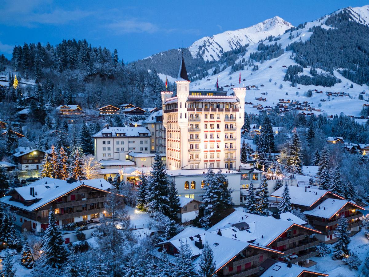 Gstaad Palace Hotel: vista dell'hotel circondato dalla cittadina e dalle montagne innevate