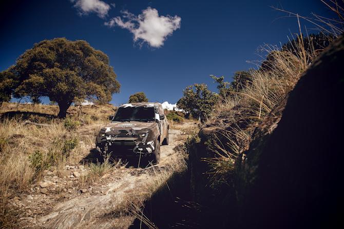 Land Rover Defender con livrea animalier supera una pendenza rocciosa