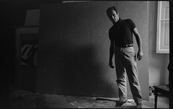 """_ Mario Schifano nel suo studio davanti all'opera """"Qualcos'altro"""", Roma 1962 Courtesy © Archivio Mario Schifano"""