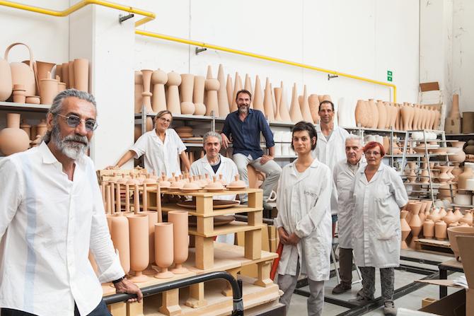 Massimo Monini (primo da sinistra) è l'attuale titolare della Rometti Ceramiche. Insieme al direttore artistico Jean Christophe Clair (con la camicia blu) e alle maestranze dell'azienda, ha rivitalizzato la produzione di questa storica manifattura. Nella foto, scattata nel laboratorio, si riconoscono le iconiche forme «a biscotto» pronte per la decorazione. Courtesy Rometti Ceramiche