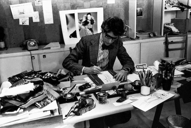 Yves Saint Laurent à son bureau, studio du 5 avenue Marceau, Paris, 1976. Photographie de Guy Marineau © Yves Saint Laurent